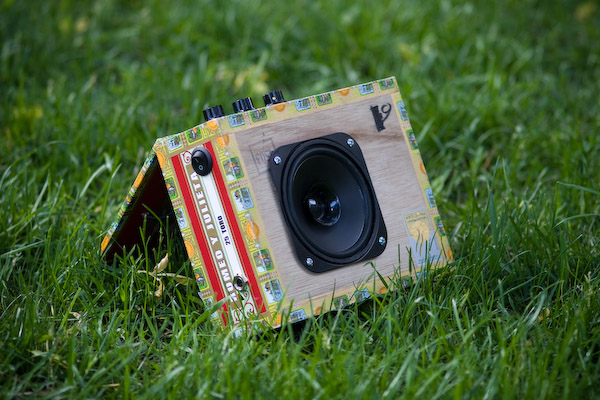 The amp on the grass, propped open with the speaker facing the camera