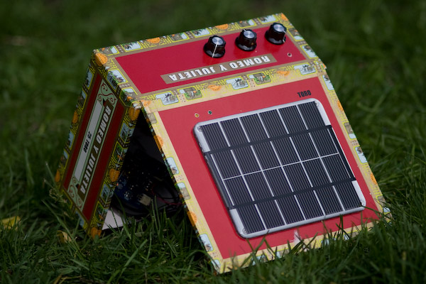 The amp on the grass, propped open with the solar panel facing the camera