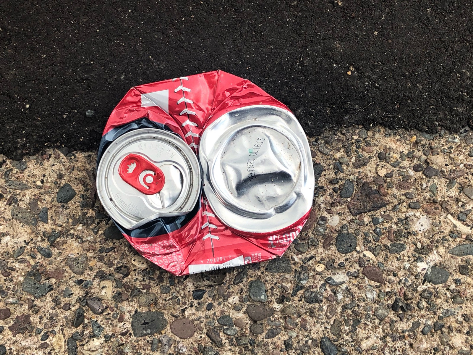 A crushed red and silver aluminum can, sitting on the road right on like line between black asphault and beige curb concrete