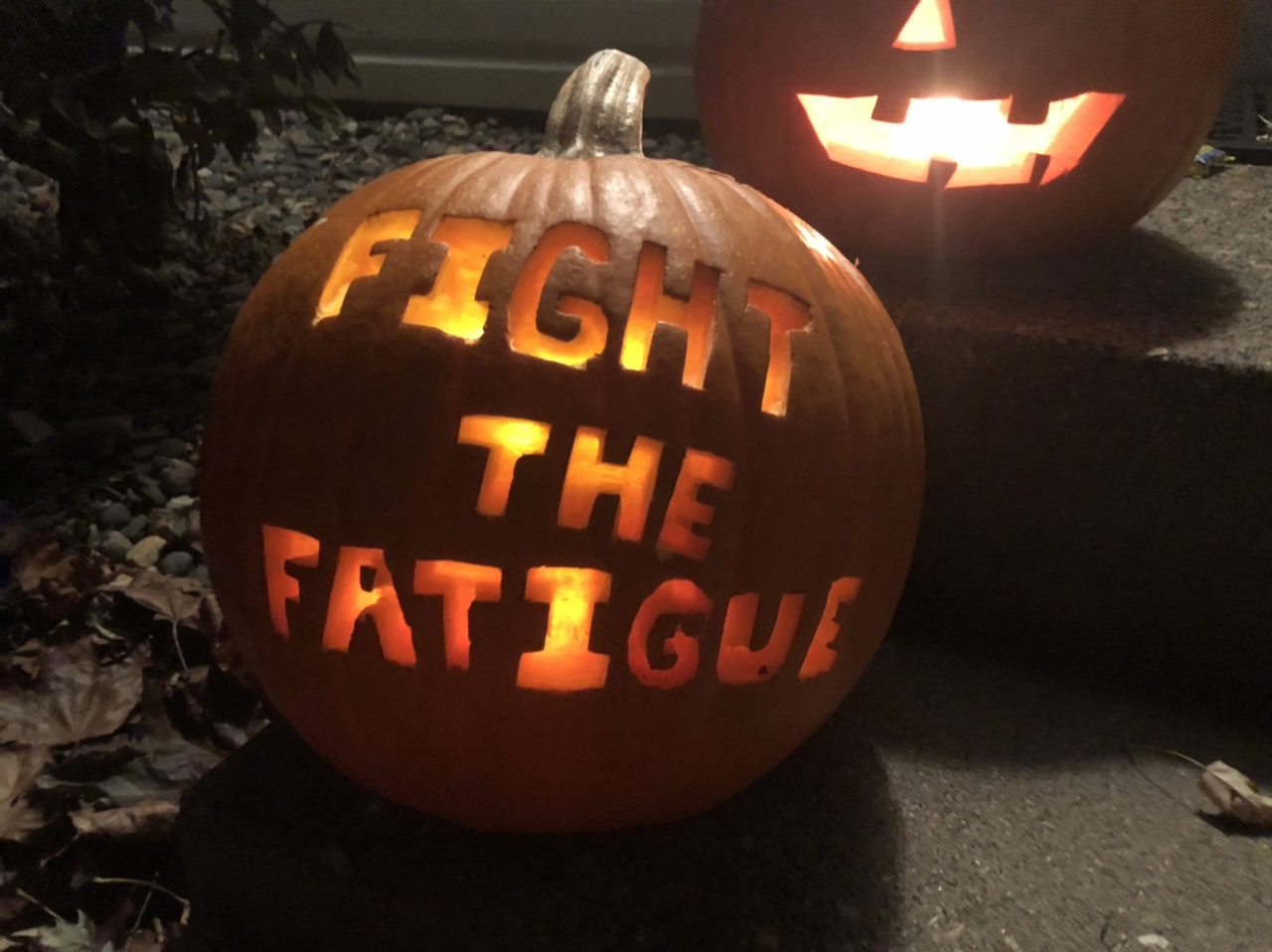 "A lit pumpkin, carved with the words ""Fight the Fatigue"""